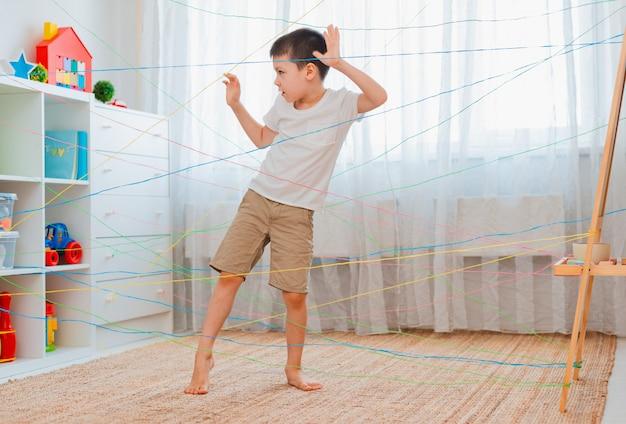 Мальчик друзья ребенок лезет через веревочную паутину, игра препятствие квест в помещении.