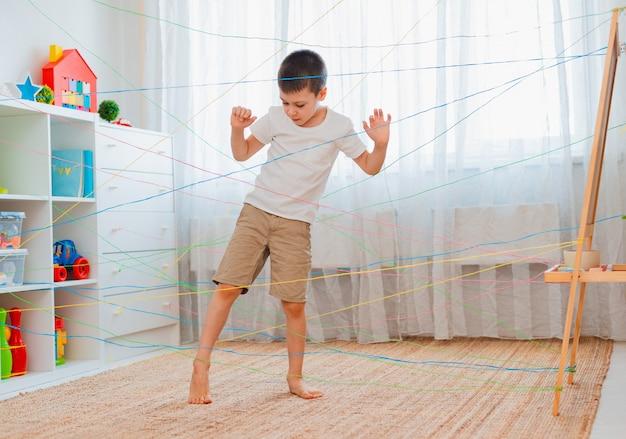 Мальчик-дружок лезет через веревочную паутину, прохождение игрового препятствия в помещении.