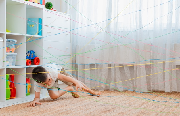 Boy friendschild climbs through a rope web,  game obstacle quest indoors.