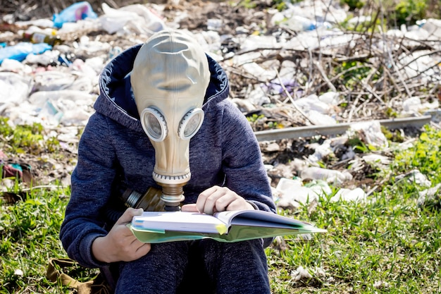 Boy in  gas mask reads  book on the background of  garbage. ecological catastrophe
