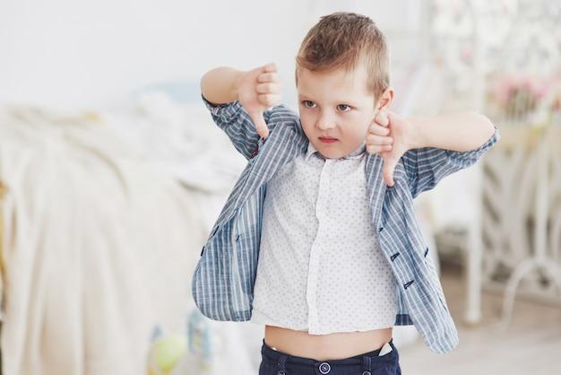 少年は指を下に振ります。感情の概念。レッスンや学校に対する彼の態度を示しています