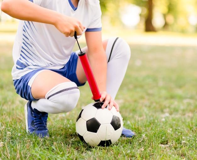 새로운 경기 클로즈업에 대 한 그의 축구를 준비하는 소년