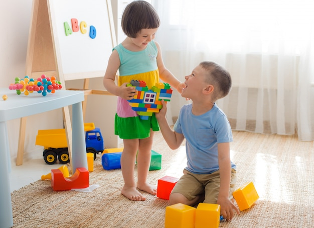 Boy and girl are holding heart made plastic blocks. brother sister have fun playing together in the room.