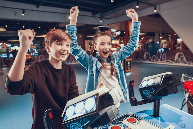 Boy and girl are piloting spacecrafts playing in arcade.