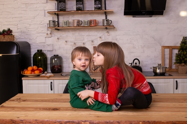 Boy and girl are sitting on kitchen table.