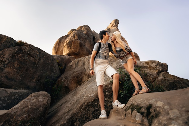 The boy and the girl are standing on the rocks and hugging