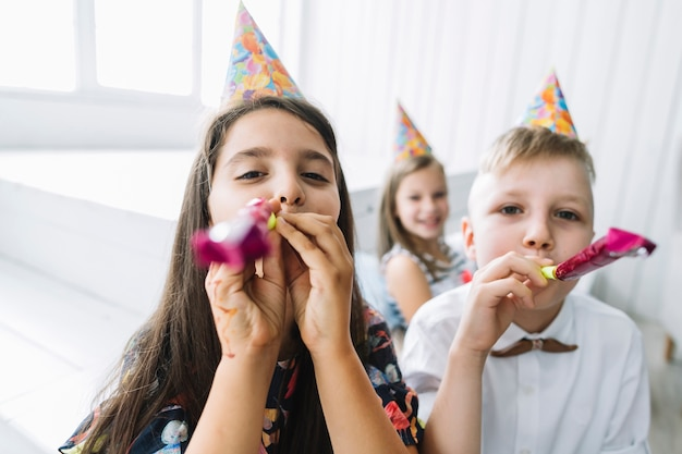 Boy and girl blowing party horns at camera
