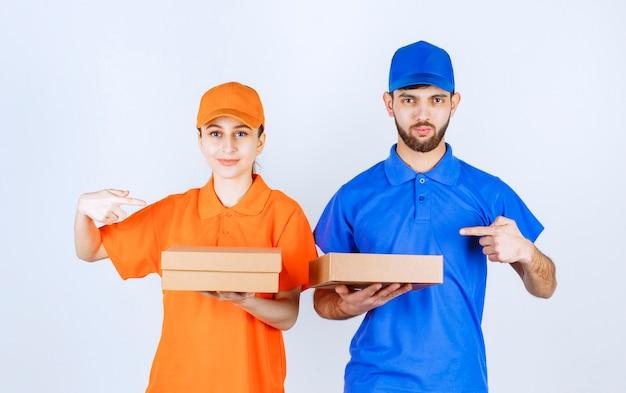 Ragazzo e ragazza in uniformi blu e gialle che tengono più pacchetti da asporto.