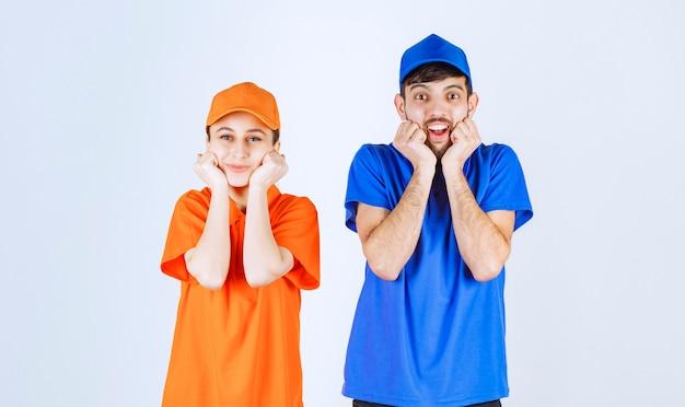 Ragazzo e ragazza in uniformi blu e gialle che mettono le mani al mento e ascoltano attentamente.