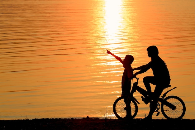 Boy and girl on bmx silhouette background.