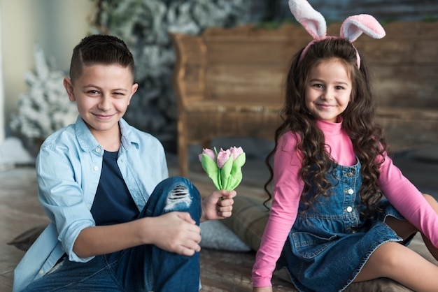Boy and girl in bunny ears with tulips