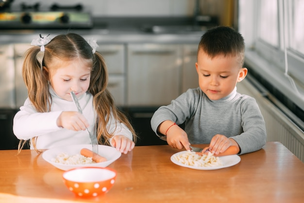 Boy and girl children in the kitchen eating sausages with pasta is very fun and friendly