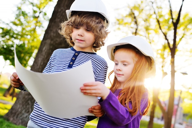 Boy and girl in construction helmets looking at white sheet of paper or drawing and smiling