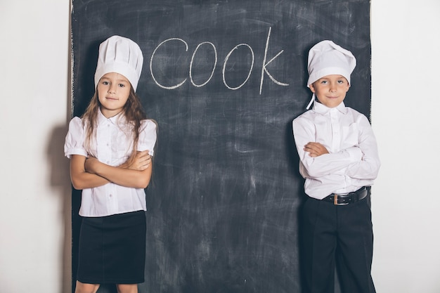 Boy and girl cooks with slate board under the text menu