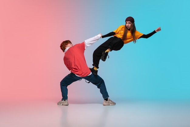 Boy and girl dancing hip-hop in stylish clothes on gradient background at dance hall in neon light.