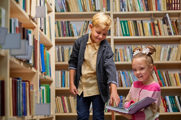 Boy and girl discussing book in school library, people lifestyles and friend education and friendship concept. leisure time for children, group activity