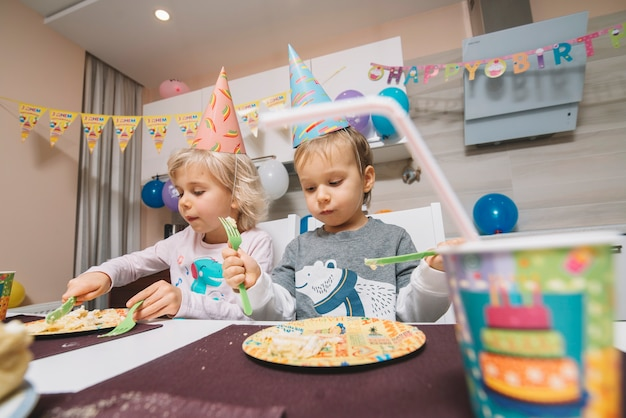 Boy and girl eating birthday cake