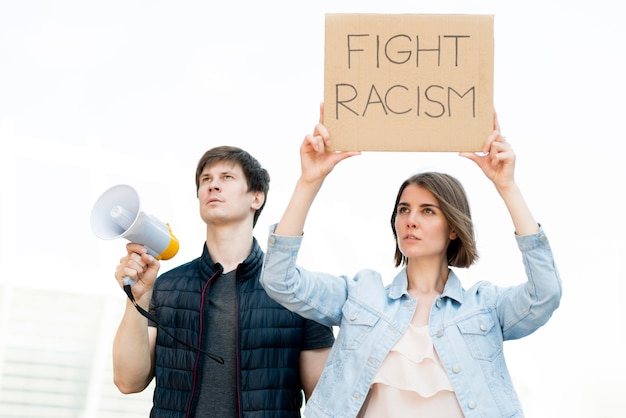Boy and girl and fight racism quote on cardboard