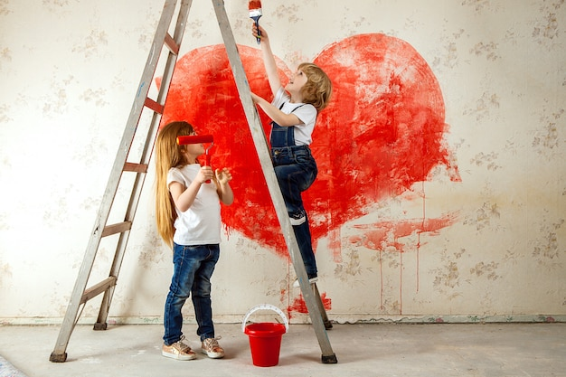 Boy and a girl in jeans and a white t-shirt, look at each other, with a paintbrush and a bucket stand on a ladder paint the wall in red, a big heart.