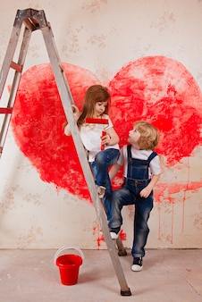 A boy and a girl in jeans and a white t-shirt, with a paintbrush and a bucket stand on a ladder paint the wall in red, a big heart.
