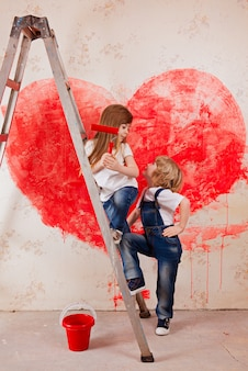 A boy and a girl in jeans and a white t-shirt, with a paintbrush and a bucket stand on a ladder
