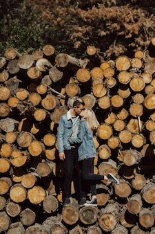 Boy and girl kissing on the stack of firewood