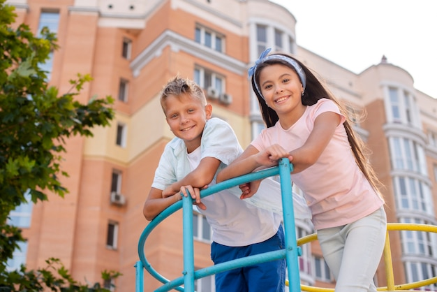 Boy and girl leaning on a metal bar