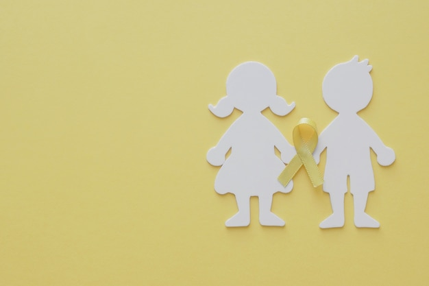 Boy and girl paper cut with yellow gold ribbon,  childhood cancer awareness