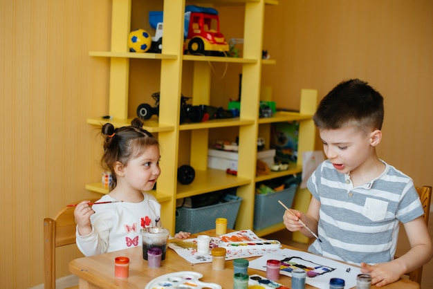A boy and a girl play together and paint. recreation and entertainment. stay at home.