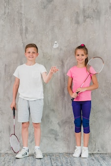 Boy and girl players with rackets and shuttlecock against concrete backdrop