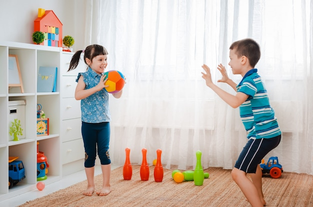 Boy and girl playing in a children's game room, throwing a ball. the concept of interaction of todlers, communication, mutual play, quarantine, self-isolation at home