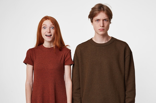 Boy and girl pose, depict different emotions.