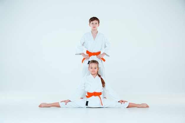 The boy and girl posing at aikido training in martial arts school. healthy lifestyle and sports concept