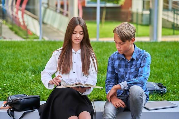 Boy and a girl read a book.