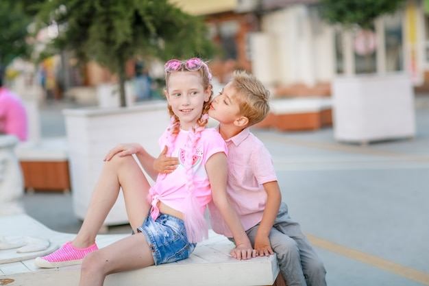 Boy and girl relatives sitting in the park on a white bench