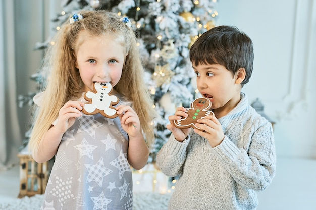 Boy and girl sit on floor under christmas tree. children eat ginger man. waiting for christmas. celebration. new year.