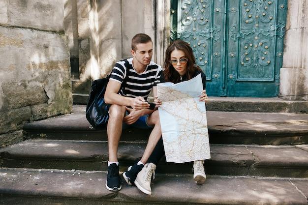Il ragazzo e la ragazza si siedono sui punti alla cattedrale con la mappa del touristc e guardano qualcosa nello smartphone