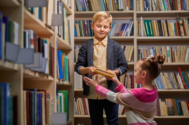 Boy and girl stand talking in library, discussing books, choose books for school. stand between bookshelves