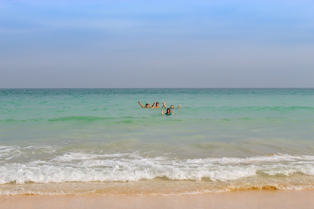 A boy and a girl standing in a sea of hands photographed at cabana beach in chumphon