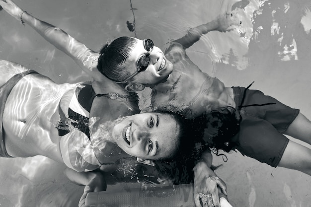 Boy and girl on a swimming pool, top view, black and white image