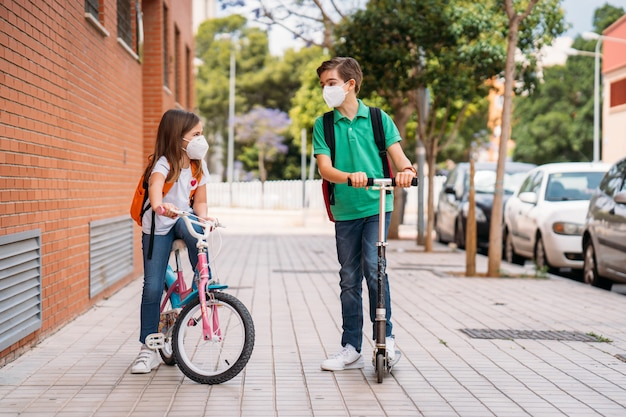 Boy and girl wearing masks and riding a scooter and bicycle on street