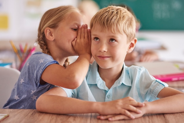 Boy and girl whispering in classroom