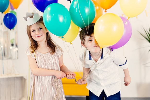 Boy and girl with balloons smiling