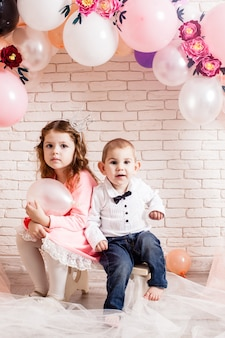 Boy and girl with crowns under birthday balloon and paper flower arch decorations. childish photozone for celebration