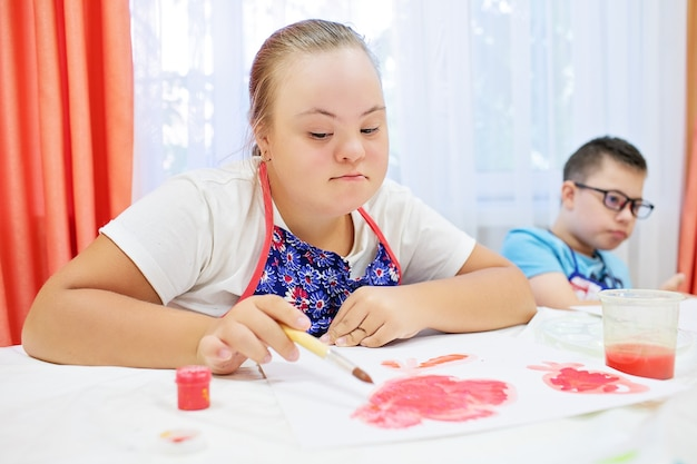 Boy and girl with down syndrome draw at a table on a white background. high quality photo