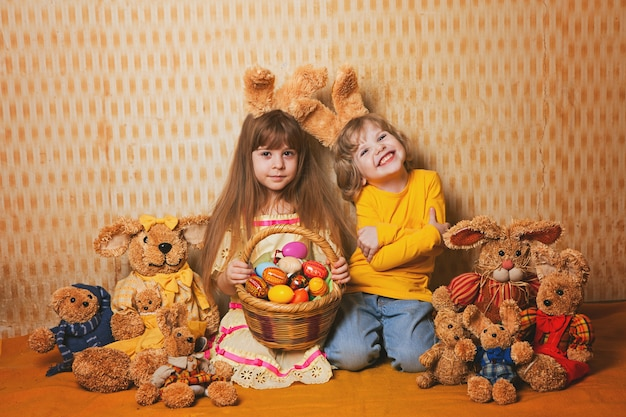 Boy and girl with rabbit ears sitting around a lot of straw and plush hares, vintage style.