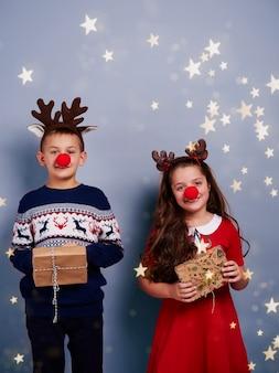 Ragazzo e ragazza con il contenitore di regalo della tenuta del corno della renna