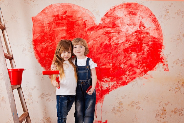 A boy and a girl with a roller in jeans and a white t-shirt, a brush and a bucket paint the wall in red.