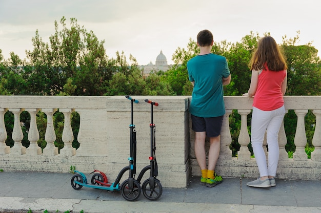 Boy and girl with their push scooters against the vatican in the park villa borghese.