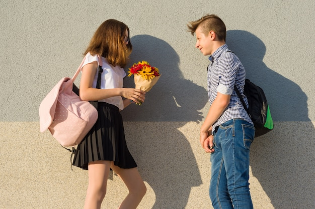 Boy gives girl bouquet of flowers. outdoor portrait of couple teenagers.